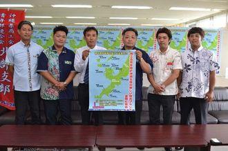 11月に発売する旅行パックをPRする仲尾圭司委員長(右から3人目)ら=16日、県庁