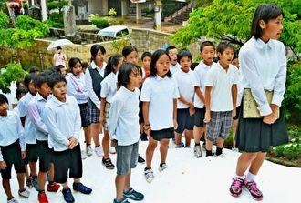 雨の中、「いのちの歌」を合唱する天妃小の児童たち=19日、那覇市若狭・小桜の塔