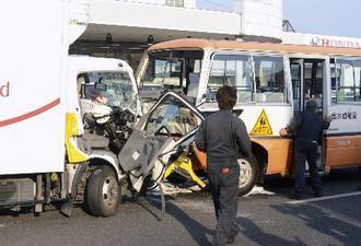 国道で衝突したトラックと送迎バス=22日、熊本市中央区