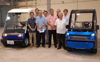 県内での製造が始まる電気自動車と開発に携わったメンバーら=17日、うるま市・ものづくりネットワーク沖縄