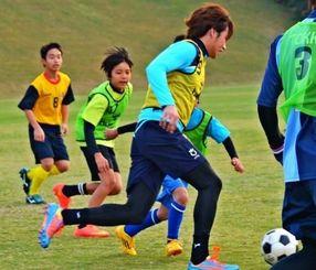 Jリーガーとミニゲームを楽しむサッカー少年ら=恩納村赤間運動公園(提供)