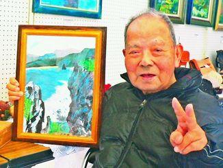 「辺戸岬」の絵画を手にする平良太郎さん=名護市・大東区公民館
