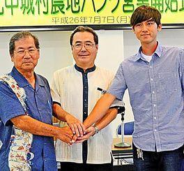 農地バンクで契約第1号となった城間建人さん(右)と嘉手川繁正さん(左)。中央は新垣頭取=北中城村役場