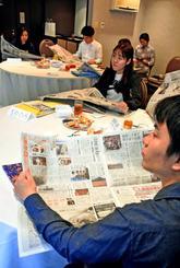 新聞を仕事に生かすコツを聞き、気になる記事を探す受講者=6日、那覇市のANAクラウンプラザホテル沖縄ハーバービュー
