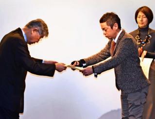 メディア・アンビシャス世話人の萩本和之さん(左)から表彰状を受け取る伊集竜太郎記者=4日、札幌市内