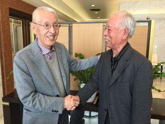 上原正三さん(左)と会い、固く握手を交わす普久原朝輝さん=4月19日、東京都内
