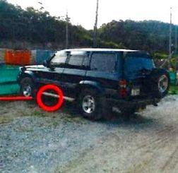 左側面にへこんで、塗装のはがれた跡(赤い円内)のある車両(恩納村役場提供)