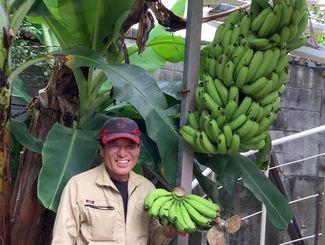 たわわに実ったバナナの木を横に笑顔を見せる我謝宏さん=西原町翁長