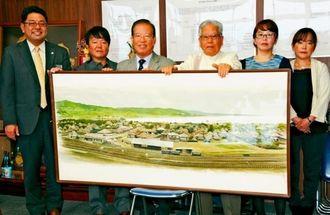 与那原駅舎が描かれた水彩画を寄贈した新城喜一さん(右から3人目)=3日、与那原町役場
