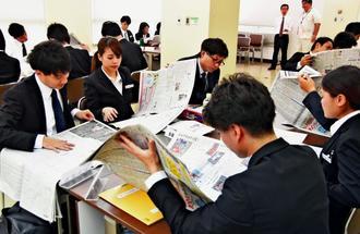 真剣な表情で新聞を読む新入社員たち=浦添市・沖縄トヨタ自動車本社