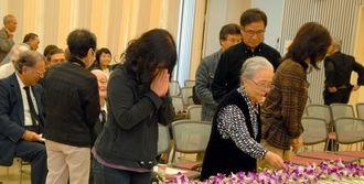 中村文子さんの遺影を掲げた祭壇に献花する参加者ら=8日、那覇市おもろまち