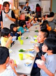 スマイルカフェで沖縄そばとおにぎりを食べる子どもたち=1日、うるま市・みどり町児童センター