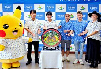 うるま市に贈られた「ポケふた」を披露する中村正人市長(右から5人目)とHYのメンバーら=22日、うるま市役所