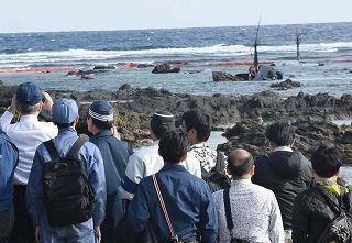 オスプレイの機体の残骸を双眼鏡で確認する翁長雄志知事(左)=18日午後3時14分、名護市安部