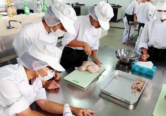 チキンを解体しスープの試作品作りをする生徒たち=2018年10月2日、県立中部農林高校(ノイズ・バリュー社提供)