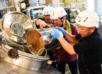 仕込槽に原料の麦芽を入れる商店連合会メンバー=8月30日、名護市東江のオリオンビール工場