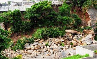 大雨で崩れた斜面の擁壁。写真下に倒れた電柱がある=10日午後4時半、南風原町新川の那覇・南風原クリーンセンター(堀川幸太郎撮影)