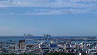青空の下、船が出入りする那覇港。