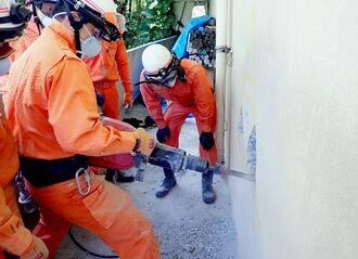 機材を使ってコンクリート壁に穴を開ける隊員ら=3月27日、北中城村内(提供)