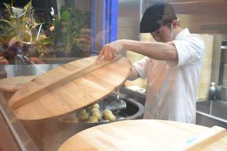 台湾の職人が蒸し焼き上げる「台湾爆噴(バオプン)小籠包」=6日、那覇市松尾の同店