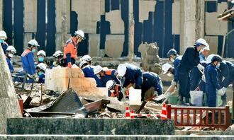 首里城火災現場のがれきを片づける県警捜査員や消防隊員。同日の作業で2つの収蔵庫が開けられた=2日午後1時20分、那覇市・首里城公園(下地広也撮影)