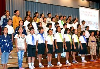 海外に移民した県系人と県民とのつながりを伝える演劇で「heiwaの鐘」を合唱する児童=15日、読谷村・喜名小学校