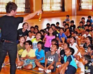 ペットボトルとカードを使ったMASAさん(左)の本場マジックに歓声を上げる宮良小の児童ら