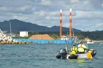 土砂を積んで護岸に近づく台船(奥)=26日午前10時5分ごろ、名護市辺野古沖