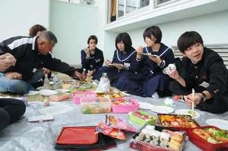昼休み時間に、保護者と一緒に弁当を食べて午後の試験に臨む受験生=6日、宮古高校