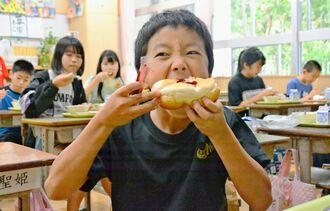 桑の実ジャムを付けたパンを頰張る港川小の児童=17日、浦添市・港川小学校