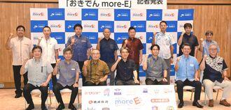 「おきでんmore E(モア・イー)」の開始をPRする沖縄電力の本永浩之社長(前列左から4人目)と提携した県内企業・団体の代表ら=7日、那覇市のおきでん那覇ビル