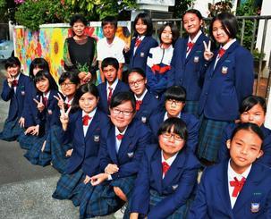 住宅の壁いっぱいに花々を描いた沖縄東中学校の美術同好会の生徒ら=26日、沖縄市泡瀬