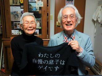 「わたしの自慢の息子はゲイです」の文字が記されたTシャツを持つ平良修さん(右)と悦美さん夫妻。悦美さんが作り、性的マイノリティーへの理解を深めるプライドパレードで着たという。大きな葛藤を経て愛香さんのセクシュアリティーを理解し、応援している=1月7日、沖縄市内の自宅