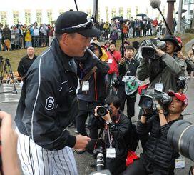 大勢の記者やファンに囲まれて球場に入る阪神の金本知憲新監督=1日、宜野座村