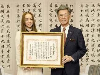 翁長雄志知事(右)から県民栄誉賞の表彰状を手渡された安室奈美恵さん=23日・沖縄県庁