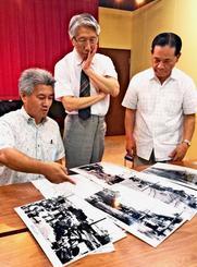 これまでに集めた東町周辺の戦前写真を眺めるサンシャイン通り会の森山紹作会長(左端)ら関係者=那覇市東町