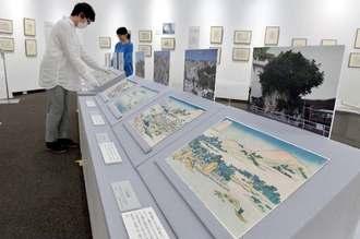 北斎が琉球の景勝地を描いた錦絵「琉球八景」を展示する学芸員=13日、浦添市美術館(下地広也撮影)