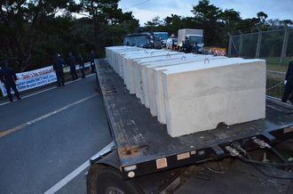 コンクリートブロックを搬入するトラック=16日午前5時45分、東村高江の北部訓練場メインゲート