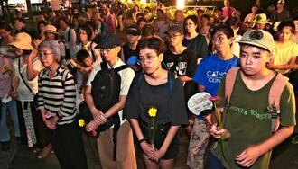 花を手に性暴力撲滅を訴える参加者=11日午後7時すぎ、那覇市・県民広場