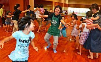 わらべ歌を歌いながら、鬼が子どもをさらおうとするのを防ぐ「子取り鬼」を楽しむ親子たち=石垣市総合体育館武道場
