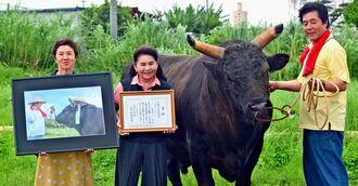 佐久川政秀さん(右)に受賞を報告した新垣フミ子さん(中央)と、牛仲間の安慶名峰子さん=読谷村古堅