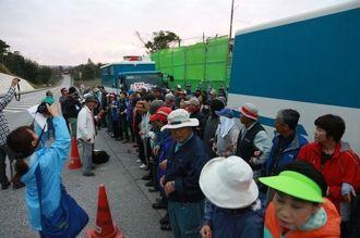 腕を組んで、「沖縄を返せ」などを歌い上げる参加者=22日午前7時半ごろ、名護市辺野古の米軍キャンプ・シュワブのゲート前