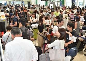 台風接近を受け、空港には早めの便を求める人が訪れ混雑した=30日午前11時20分、那覇空港