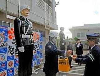 大城辰男署長(右)から警視待遇巡査部長の昇任辞令を受け取る「宮古島まもる君」に扮した署員=8日、宮古島署