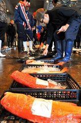 糸満漁業協同組合の初競りで、魚介類を競り落とす仲買人たち=5日、糸満市西崎の糸満漁協セリ市場