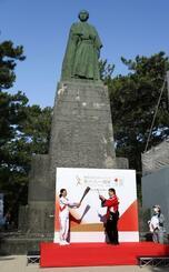 坂本龍馬像前でトーチを掲げる島崎和歌子さん(左)=19日午前、高知市