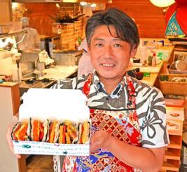 バラエティー豊かな食材を挟んだポーク卵おにぎりを見せる「ポークたまごおにぎり本店」の清川勝朗代表=那覇市の同本店