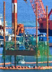 新たな地点で、掘削する棒を降ろし(中央)ボーリング調査をするスパット台船=13日午後、名護市・大浦湾(伊藤桃子撮影)