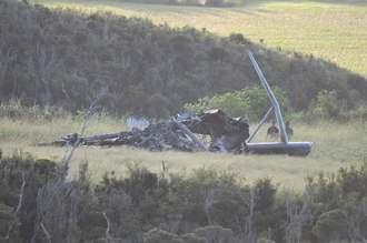 事故から一夜明けた現場。機体の残がいの近くでは米軍や県警の関係者が警戒に当たる=12日午前7時4分、東村高江