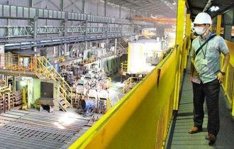 仕上がった鉄筋を広げて冷ます工程を見る見学者=1日、沖縄市海邦町・拓南製鐵の新中城工場